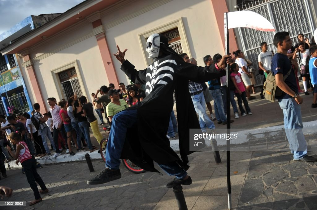 A man with a skull mask participates in the 'Burial of arrogance and haughtiness' carnival during the IX Poetry Festival in Granada, 45 km from Managua, Nicaragua on February 20, 2013. In this occasion the festival is dedicated to Nicaraguan poet Ernesto Cardenal. AFP PHOTO/Hector RETAMAL