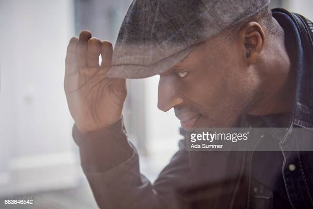 man with a slide cap leaning on a window and looking through