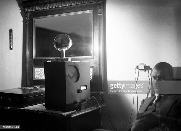 A man with a stern expression sits in a dark room and listens to a large radio which sits on a desk as a small lamp on top of the radio reflects on a...