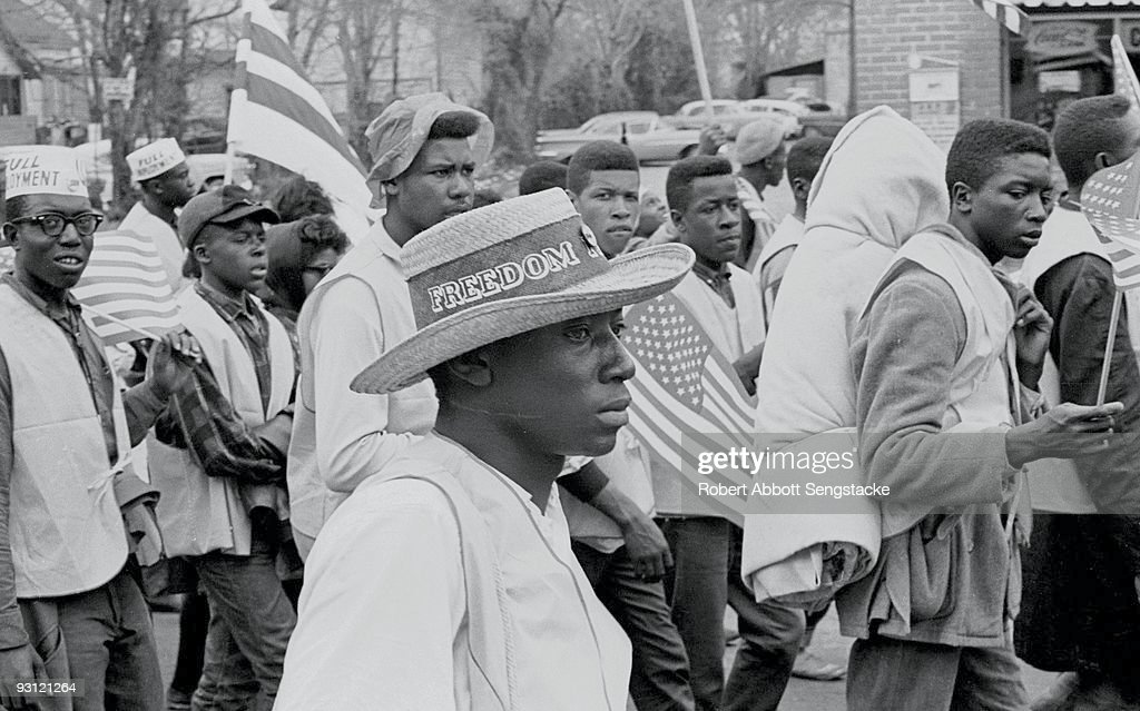 A man with a straw hat that reads 'Freedom' on its band walks with others during on the Selma to Montgomery marches held in support of voter rights, Alabama, late March, 1965. Several young men in the background wear paper caps that read 'Full Employment' and other marchers carry American flags.