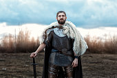 Formidable man warrior in armor and sword standing in a field and protects.