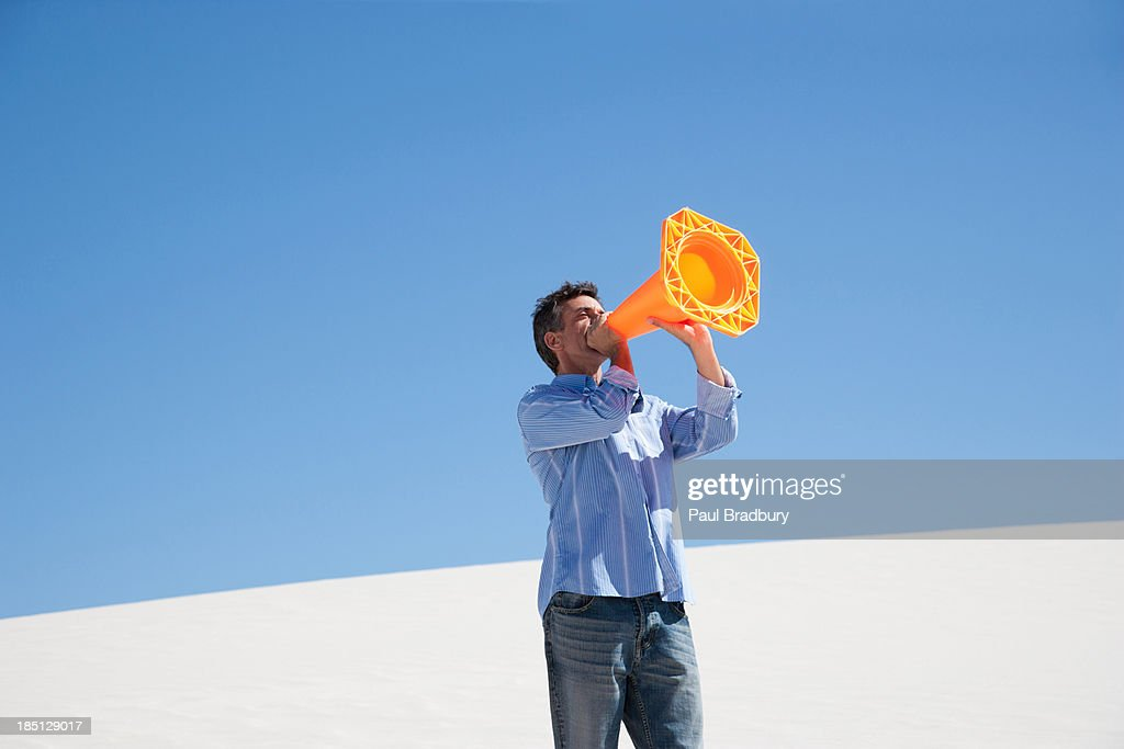 A man with a traffic cone in the middle of desert