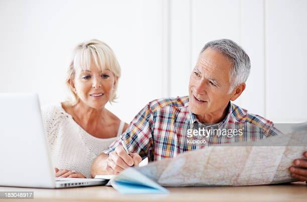 Man with a woman taking notes while looking at laptop