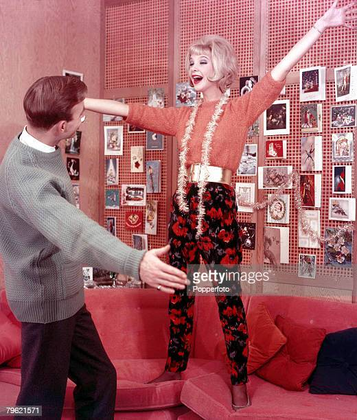 1960 A man with a woman who is standing on a sofa have their arms outstretched greeting each other both are wearing fashionable clothing whilst...