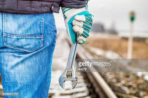 Man with adjustable wrench on the railroad : Stock Photo
