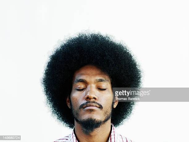 Man with afro hairstyle eyes closed chin up