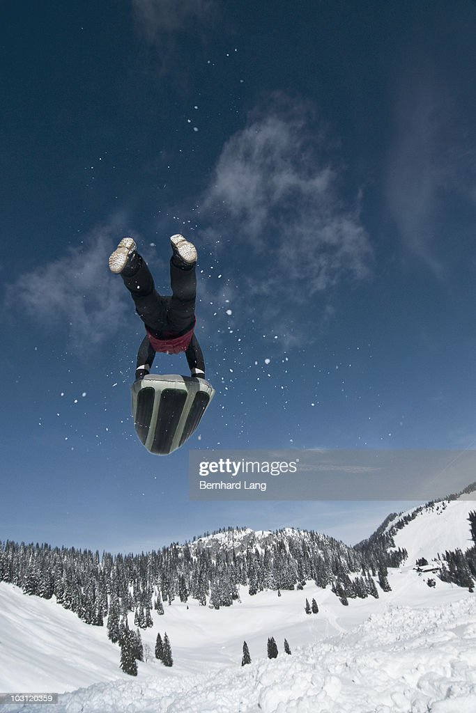 Man with airboard jumping in midair, rear view : Stock Photo