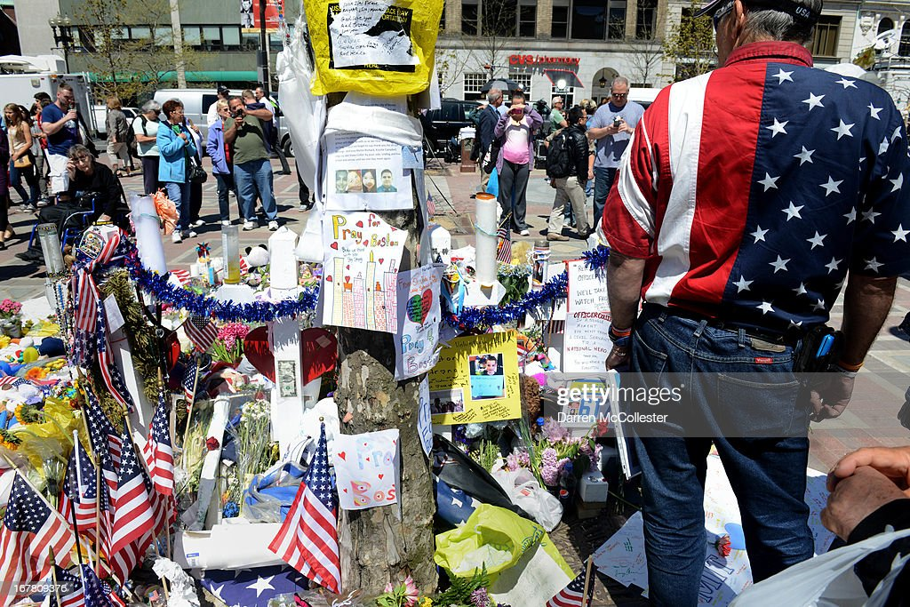 A man with an American flag shirt stands at the memorial site in Copley Square for the deadly attacks on the Boston Marathon on Boylston Street April 30, 2013 in Boston, Massachusetts. Boston continues to return to normalcy with Bolyston Street fully reopened and businesses back up and running following two weeks of closures.