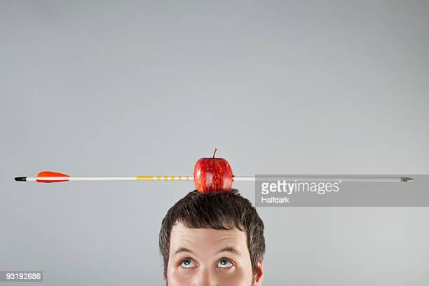 A man with an apple on top of his head and an arrow piercing it