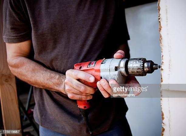 Mann mit elektrischer Schraubendreher
