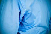 closeup of a man wearing a blue shirt with an underarm sweat stain