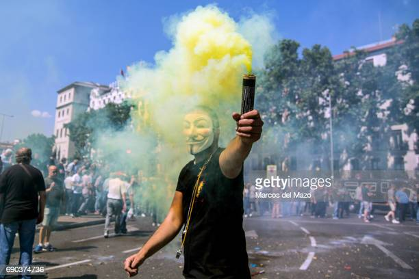 A man with anonymous mask and a smoke bomb protesting during a demonstration against private services such as Uber and Cabify demanding Government to...