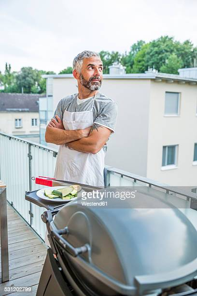 Man with apron standing on his balcony watching something
