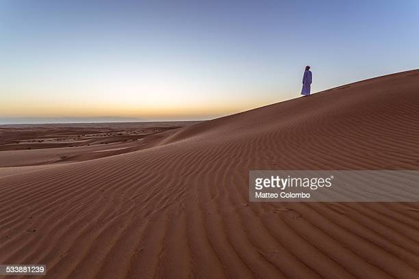 Man with arabic dress standing on sand dune, Oman
