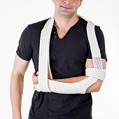 Mid Section Close Up of Man with Arm Supported in Modern Cast Sling and Standing in Studio with White Background.