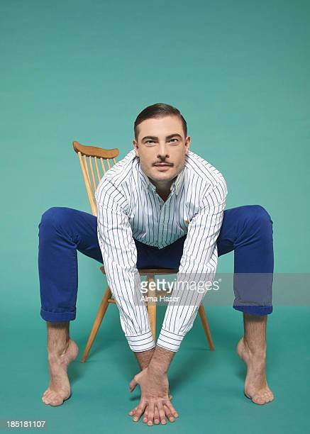 Man with arms and legs stretched over a chair