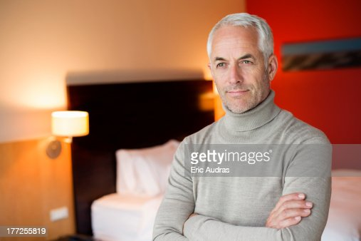 Man with arms crossed in a hotel room : Stock Photo