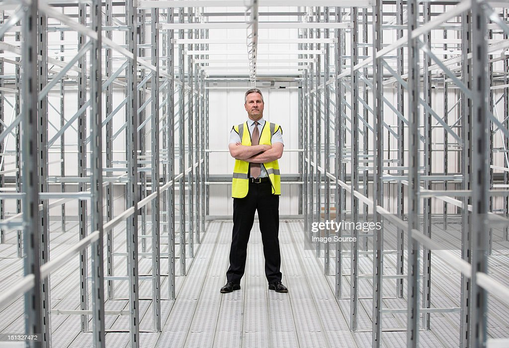 Man with arms folded in empty warehouse, portrait : Stock Photo