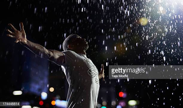man with arms in air in the rain