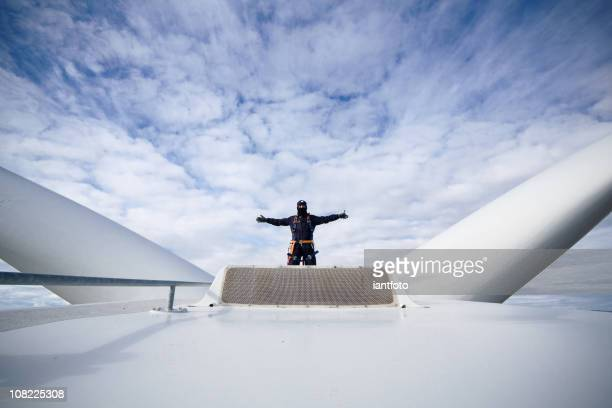 Man with arms open at work on a giant wind turbine