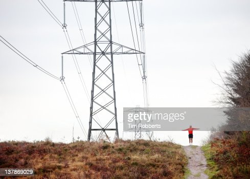 Man with arms outstretched in wild landscape. : Stock Photo