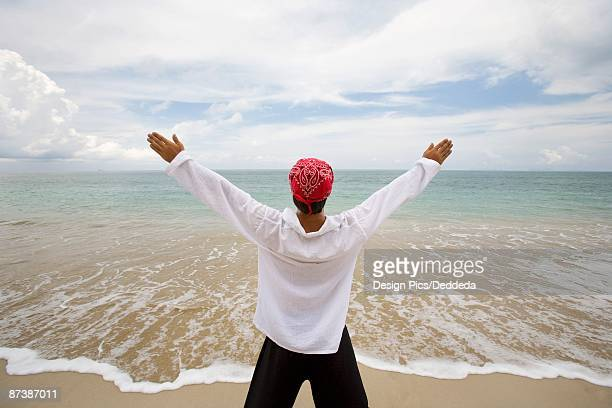 A man with arms outstretched on a beach in Koh Lanta, Thailand