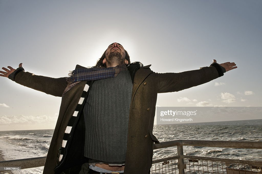 man with arms outstretched on a windy beach : Stock Photo