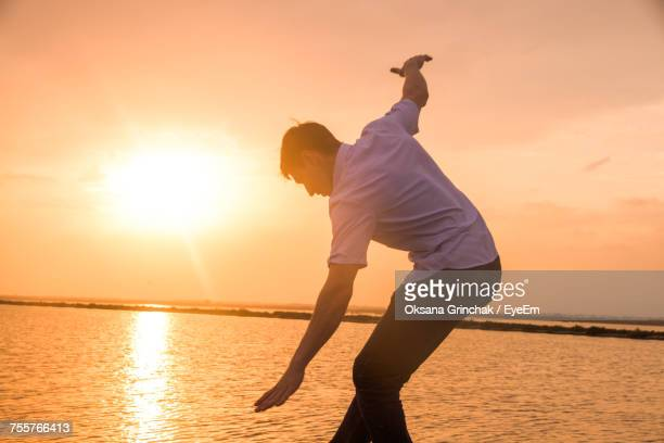 Man With Arms Outstretched Standing Against Sea During Sunset