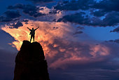 Winner man standing on the top of mountain over dramatic sky