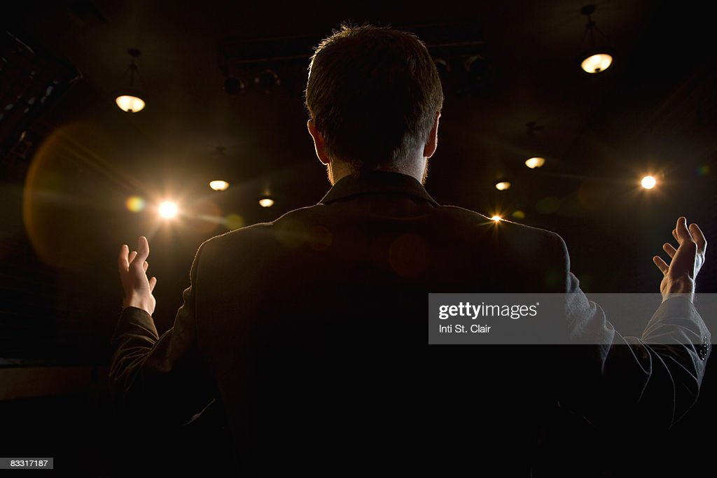 Man with arms raised looking out at audience : Stock Photo