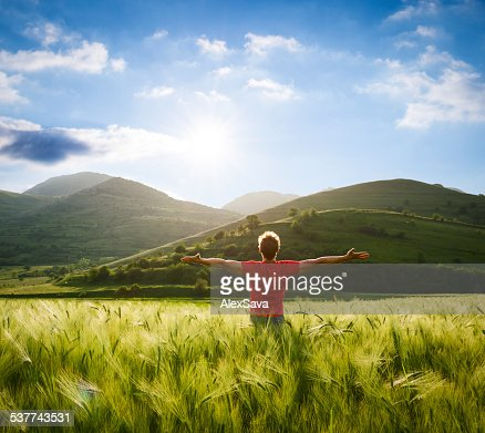 man with arms wide open in the wheat field