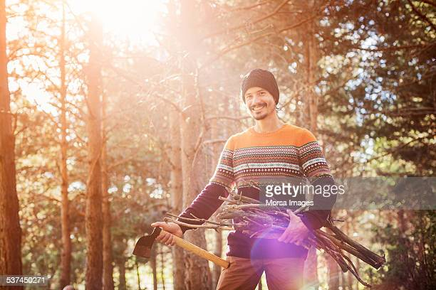 Man with axe and firewood in forest