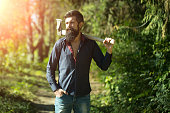 One handsome strong stylish male logger of young man with long lush black beard and moustache in shirt holding wooden axe walking in forest outdoor on natural background, horizontal picture