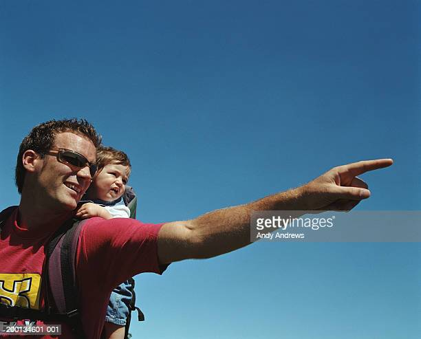 Man with baby (12-15 months) on back, pointing, close-up