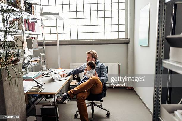 Man with baby on lap using laptop at desk in a factory