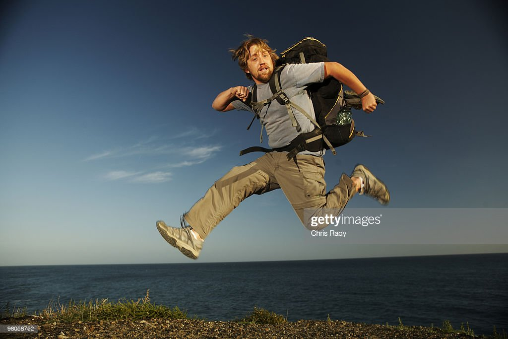 Man with backpack leaping infront of ocean. : Stock Photo