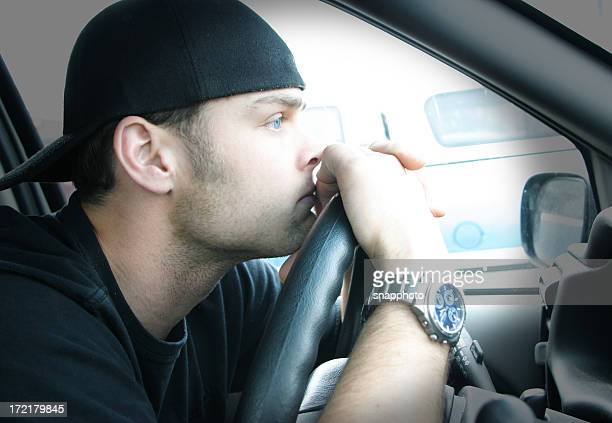Man with backward hat and face on steering wheel of a car