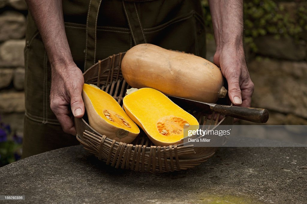Man with basket of butternut squash : Stock Photo