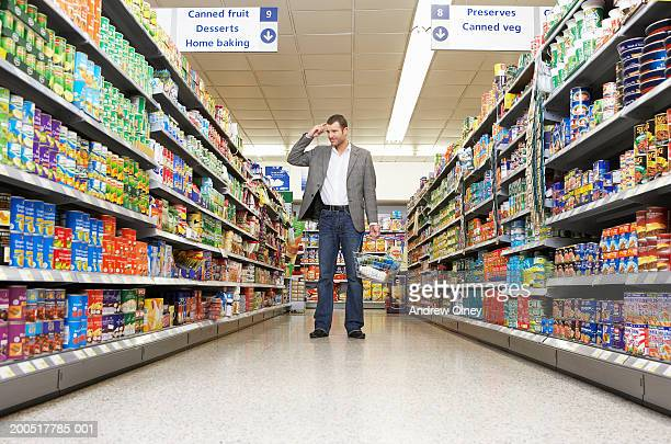 Man with basket shopping in supermarket, scratching head in aisle