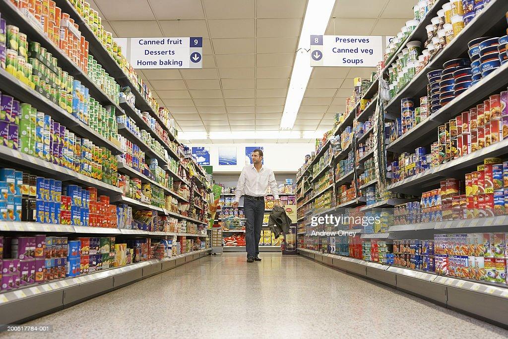 Man with basket shopping in supermarket, walking along aisle