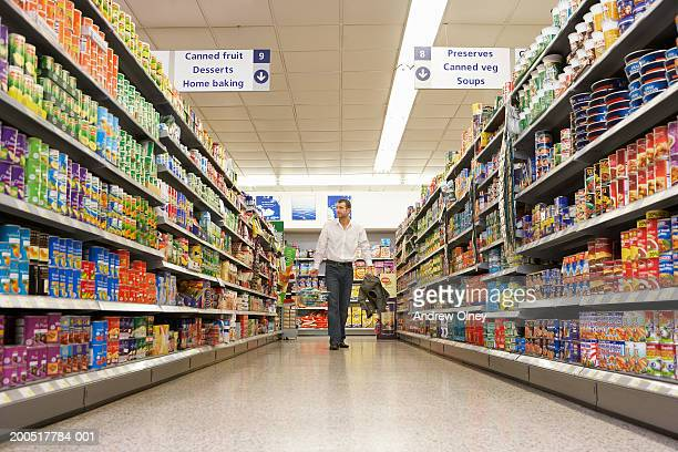Man with basket shopping in supermarket, walking along aisle