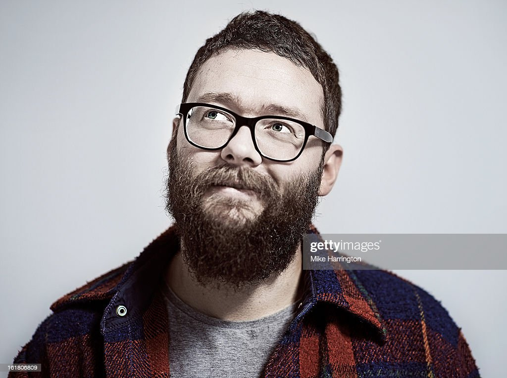 Man with beard and glasses looking up to side