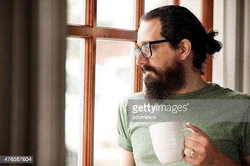 Man With Beard Holding Coffee Mug And Looking Out Window