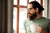 Man With Beard Holding Coffee Mug And Looking Out Window