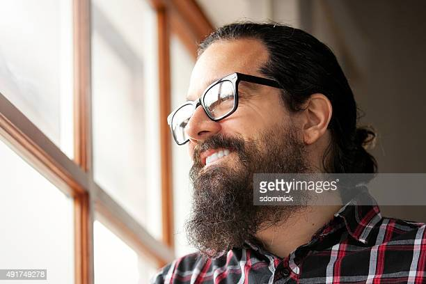 Man WIth Beard Smiling As He Looks Through Window.