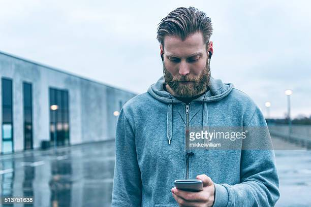 Man with beard uses smart phone outside