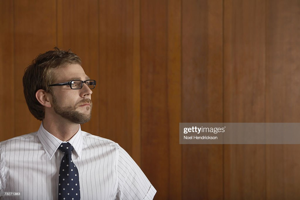 Man with beard, wearing glasses, head and shoulders, indoors : Stock Photo