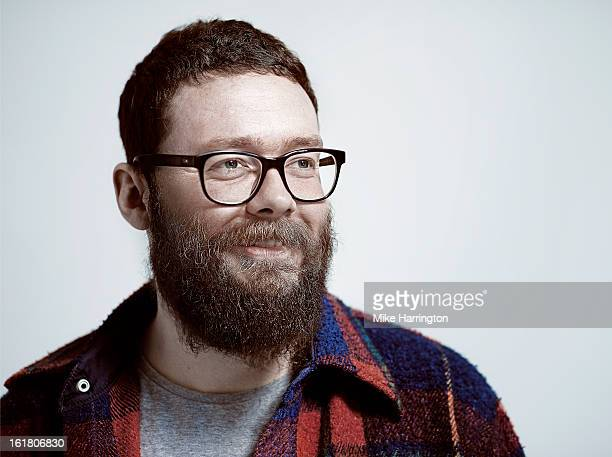 Man with beard wearing glasses smiling to side.