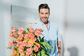 man with beautiful bouquet looking at camera