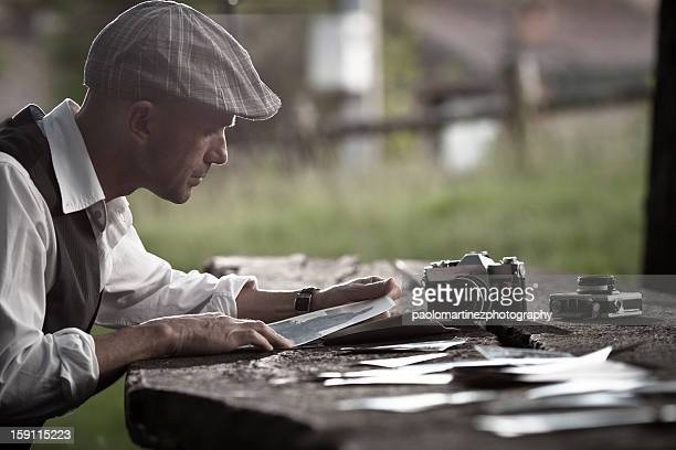 man with beret looking at old pictures